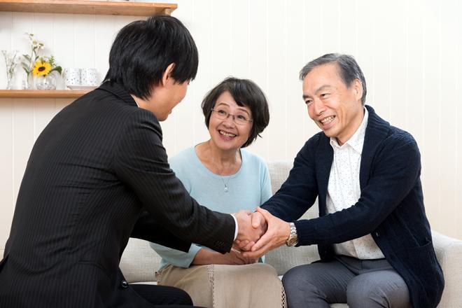 老夫婦と握手をしているビジネスマン